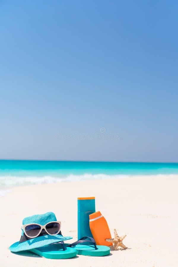 Suncreamflessen, beschermende brillen, zeester en zonnebril op witte van het zandstrand oceaan als achtergrond royalty-vrije stock foto's