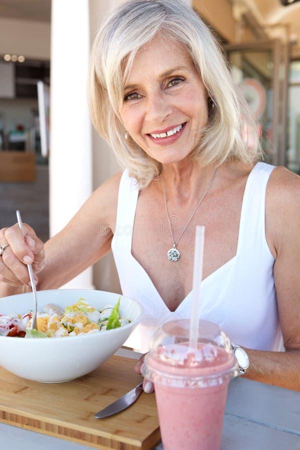 Sund äldre kvinna som äter på den utomhus- restaurangen royaltyfria bilder