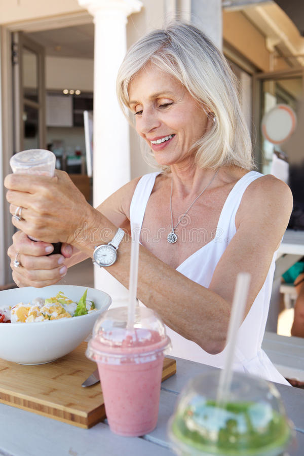 Sund äldre kvinna som äter på det utomhus- kafét arkivfoton