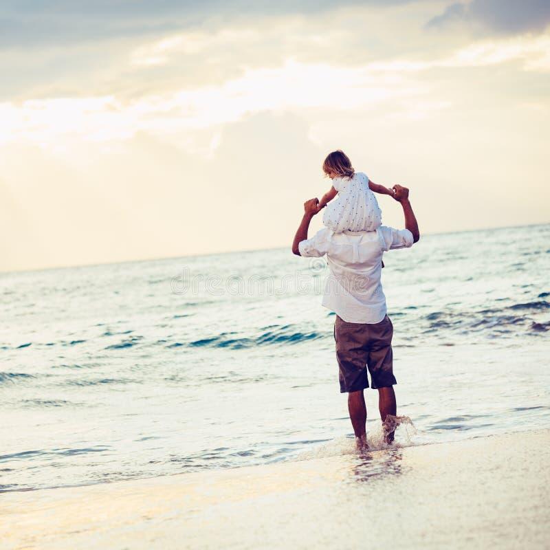 Sund älska fader och dotter som tillsammans spelar på stranden arkivfoton