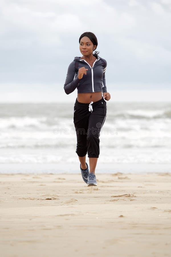Sund afrikansk amerikankvinna för full kropp som kör på sand på stranden royaltyfria bilder