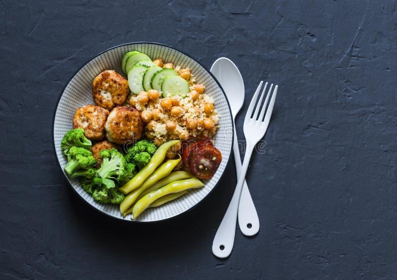 Sund allsidig buddha bunke - kryddig couscous med kikärtar, broccoli, haricot vert och kalkonköttbullar på mörk bakgrund, bästa v arkivbilder