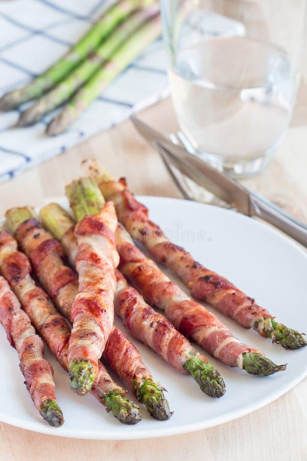 Sund aptitretare, grön sparris som slås in med bacon på en vit royaltyfri foto