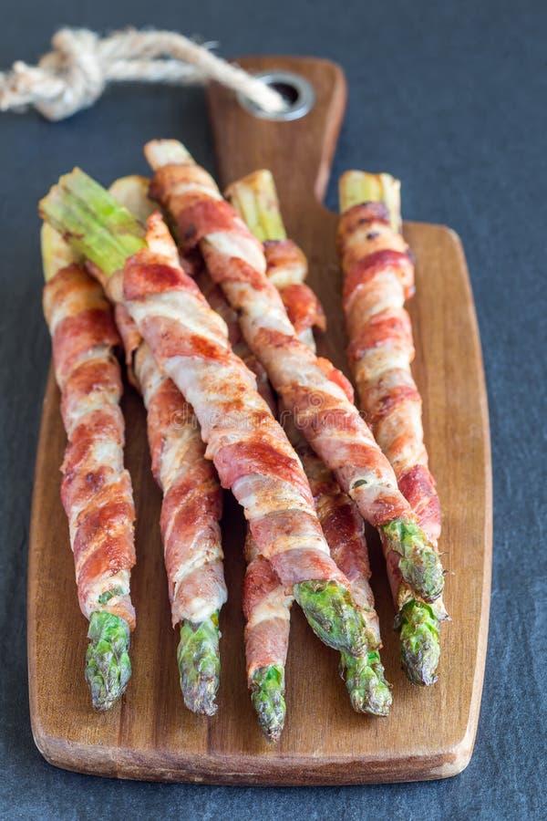 Sund aptitretare, grön sparris som slås in med bacon på en woode royaltyfri foto