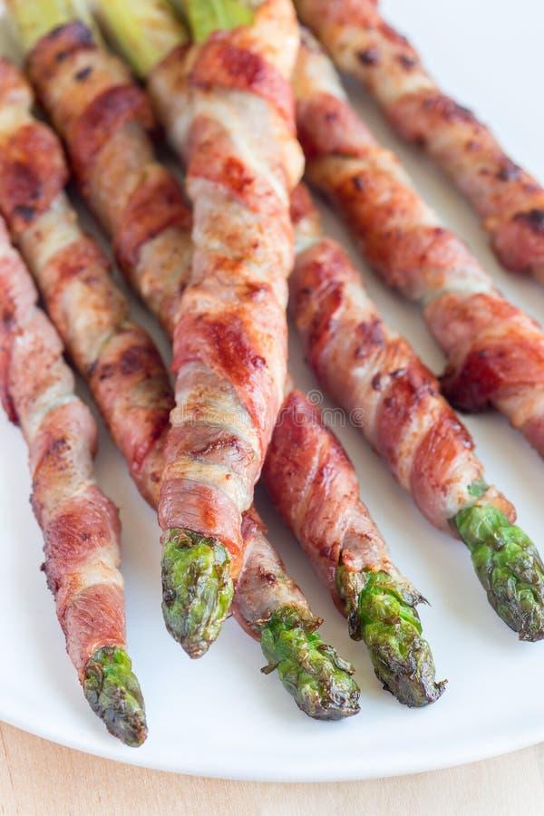 Sund aptitretare, grön sparris som slås in med bacon på vit p arkivfoton