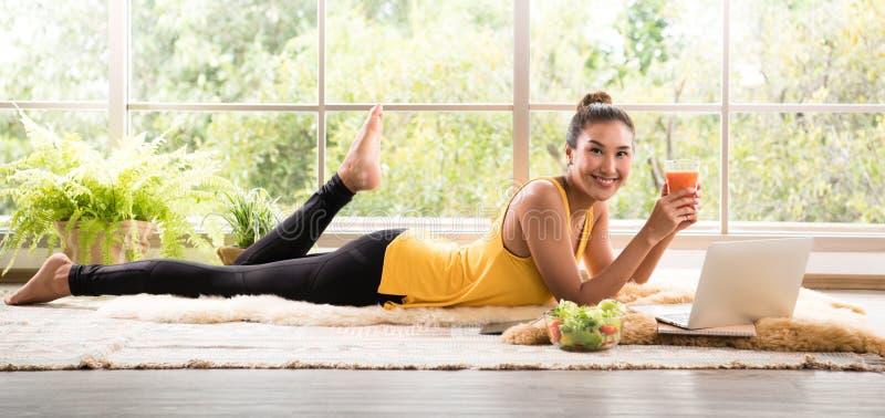 Sund asiatisk kvinna som ligger på golvet som äter sallad som ser avkopplad och bekväm arkivbild