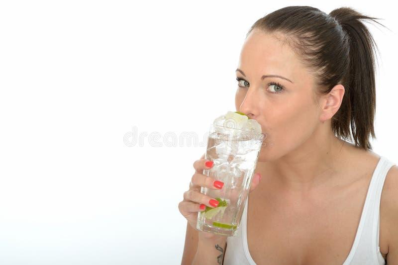 Sund attraktiv ung kvinna som rymmer ett exponeringsglas av med is vatten arkivfoto