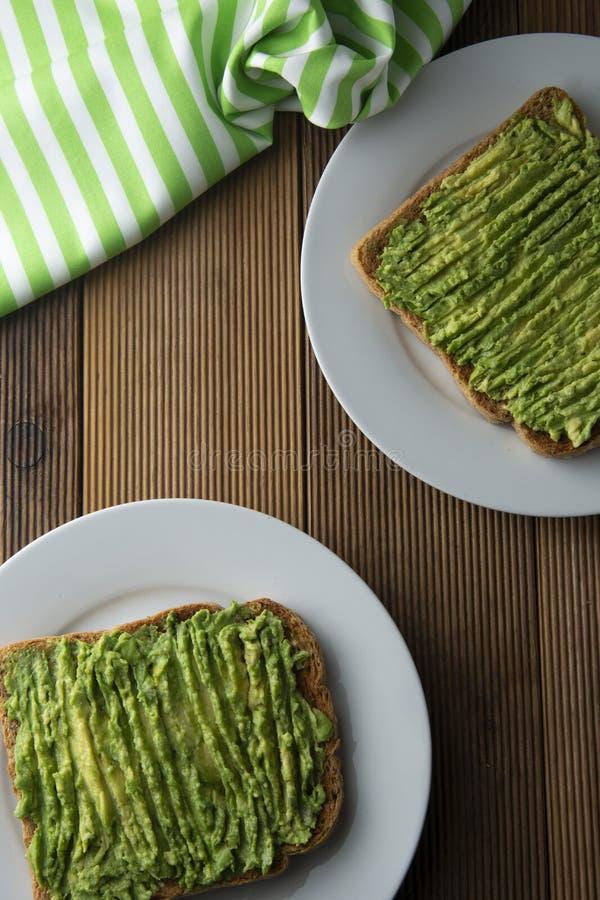 Sund avokadosmörgås, rostat brödbröd Mushed avokadodeg, på träbakgrund arkivbild