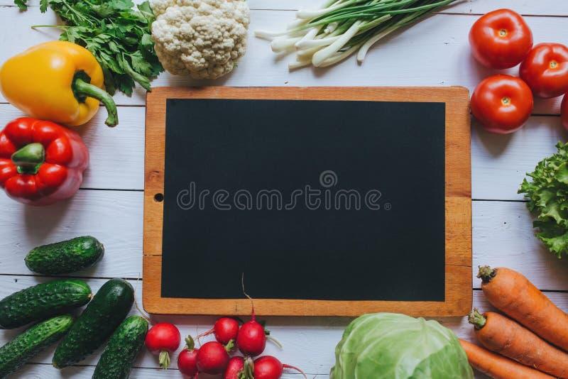 sund begreppsmat Grönsaksalladingredienser gränsar ramen Svart papper på tom utrymmebakgrund för vit trätabell organiskt royaltyfri foto