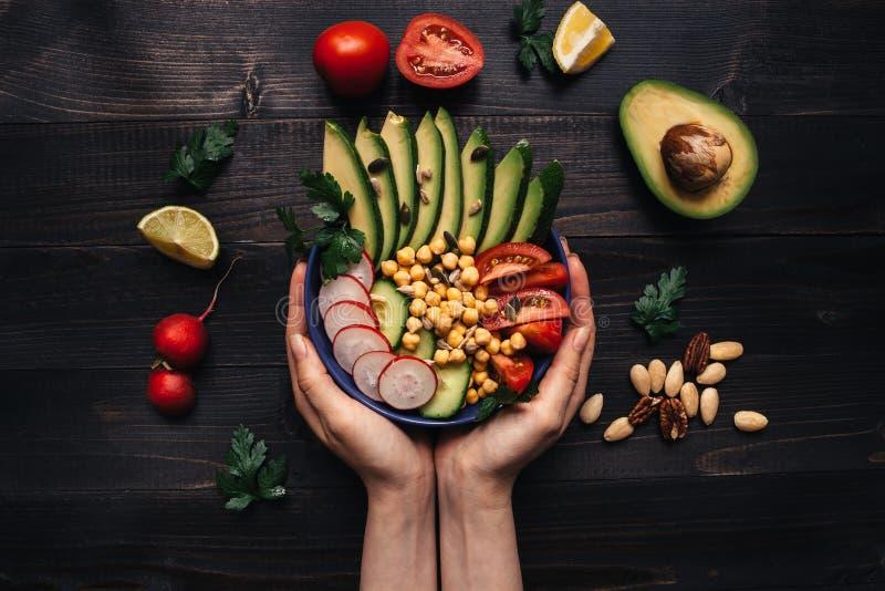 sund begreppsmat Händer som rymmer sund sallad med kikärten och grönsaker Strikt vegetarianmat banta vegetarian royaltyfri bild