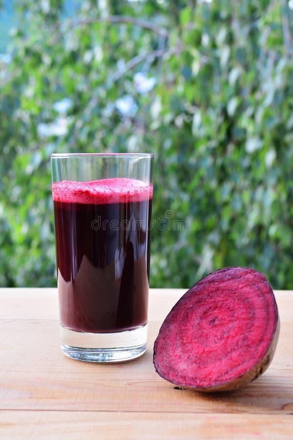 Sund betafruktsaft nytt pressande i exponeringsglas royaltyfri fotografi