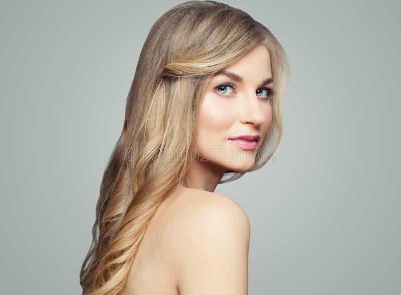 Sund blond kvinnastående Flicka med långt lockigt hår och klart hud-, skincare- och wellnessbegrepp arkivfoton