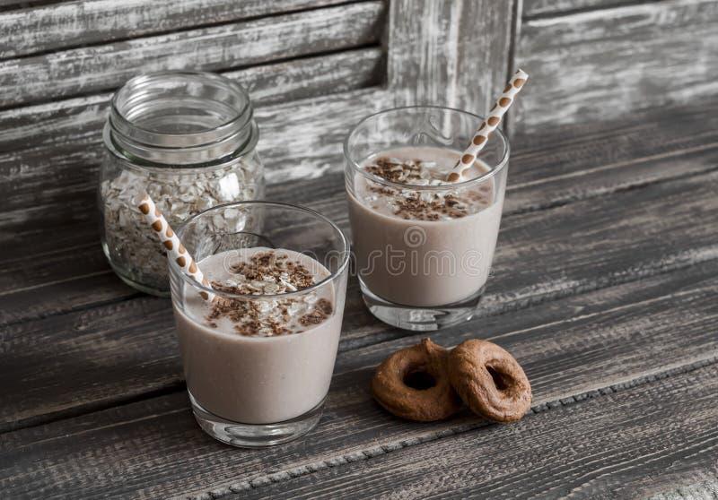 Sund drink - banan- och havremjölsmoothie i ett exponeringsglas på mörk träbakgrund arkivfoton