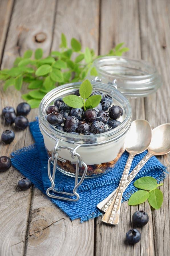 Sund efterrätt med hemlagad granola, yoghurt och blåbär royaltyfri fotografi
