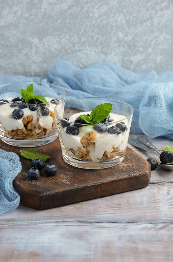 Sund efterrätt med hemlagad granola, yoghurt och blåbär royaltyfri foto