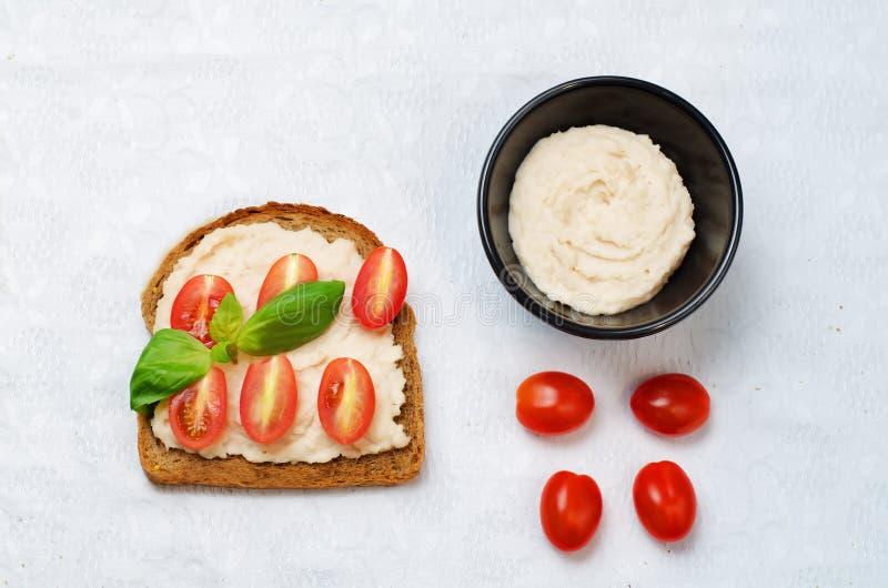 Sund för hummustomat för vit böna smörgås för frukost för råg fotografering för bildbyråer