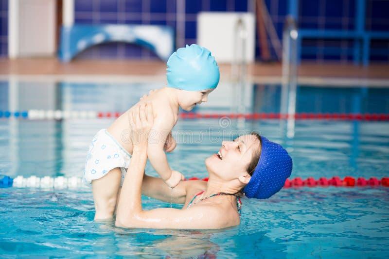 Sund familjmoderundervisning behandla som ett barn simbassängen royaltyfria foton