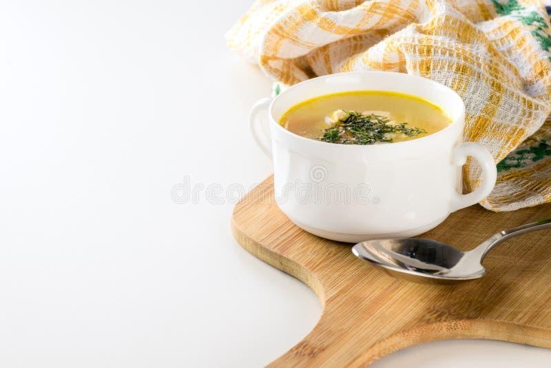 Sund feg soppa med dill i en vit bunke på en träskärbräda med metallskeden och den gula kökshandduken royaltyfria foton