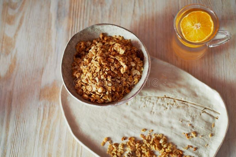 Sund frukost av mästare Mysli ett exponeringsglas av vatten med en skiva av apelsinen Keramiskt handgjort royaltyfria bilder