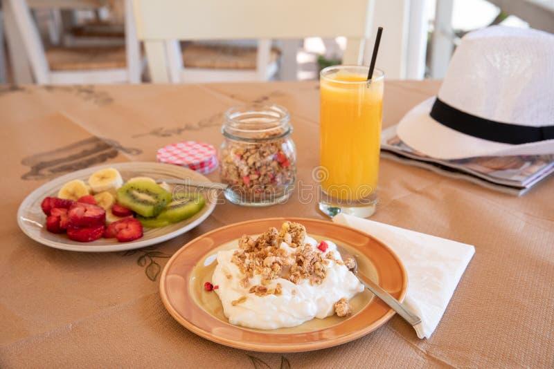 Sund frukost från yoghurt, den skivade bananen, kiwi, jordgubbar, granola och exponeringsglas av ny orange fruktsaft i ett härlig royaltyfri bild