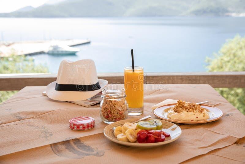 Sund frukost fr?n yoghurt, den skivade bananen, kiwi, jordgubbar, granola och exponeringsglas av ny orange fruktsaft i ett h?rlig arkivfoton