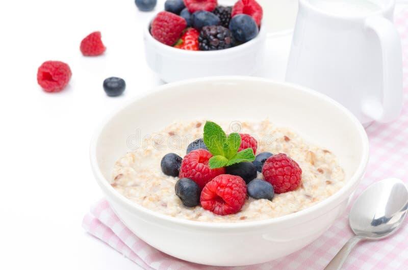 Sund frukost - havremjöl med nya bär som isoleras på vit arkivbild