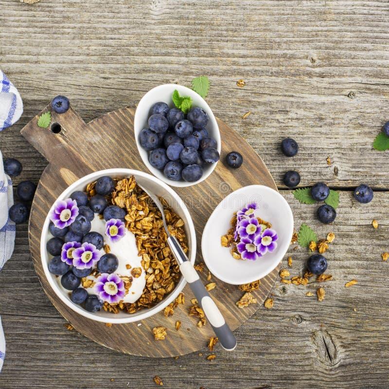 Sund frukost: hemlagad grillad granola med blåbär, kiwi och ätliga blommor på träbakgrund från arkivbild