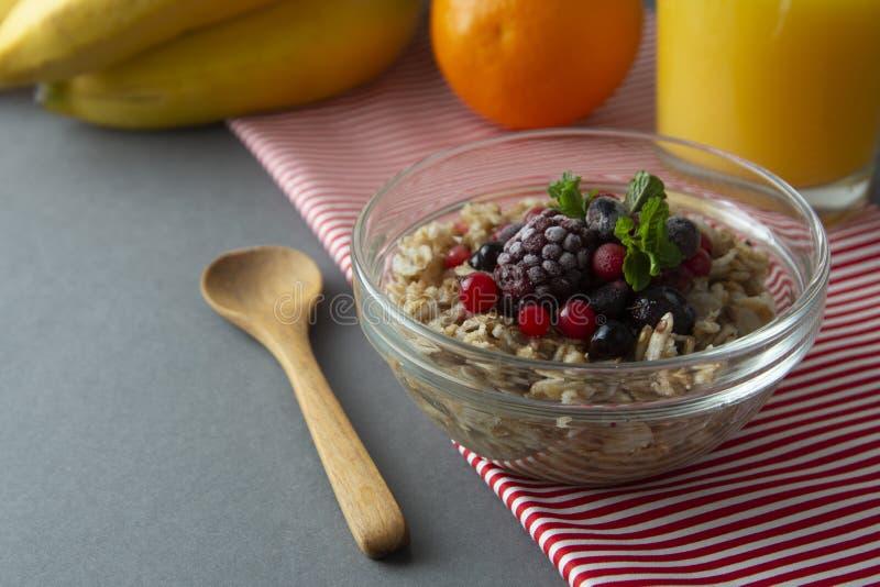 Sund frukost i en bunke med havremj?l, djupfrysta b?r, nya jordgubbar, mintkaramell Havrehavregr?t med frukter royaltyfria bilder