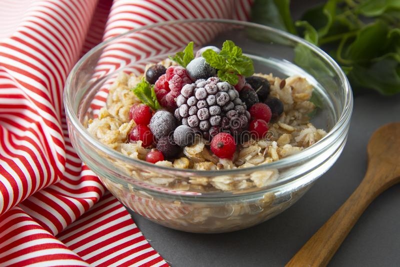 Sund frukost i en bunke med havremj?l, djupfrysta b?r, nya jordgubbar, mintkaramell Havrehavregr?t med frukter arkivbild