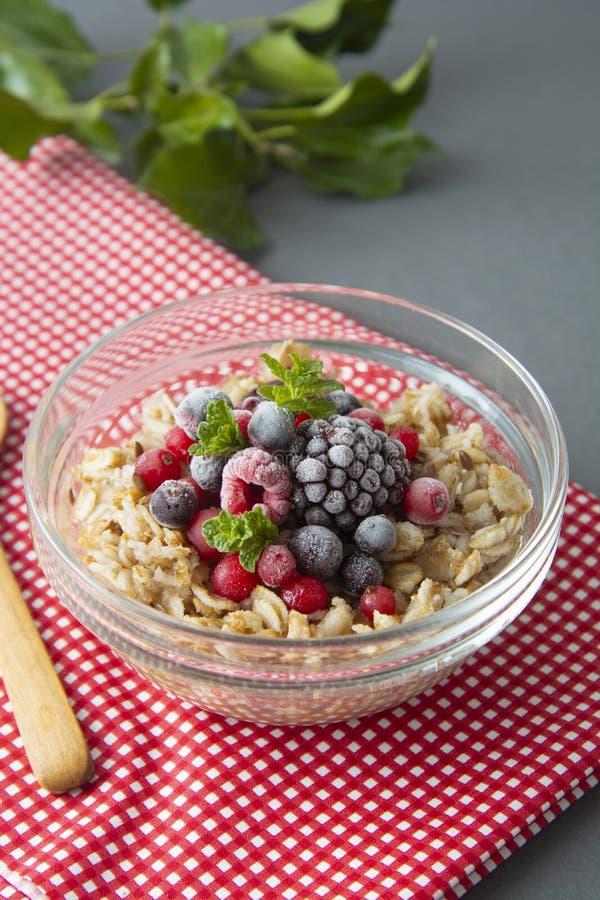 Sund frukost i en bunke med havremj?l, djupfrysta b?r, nya jordgubbar, mintkaramell Havrehavregr?t med frukter royaltyfri bild