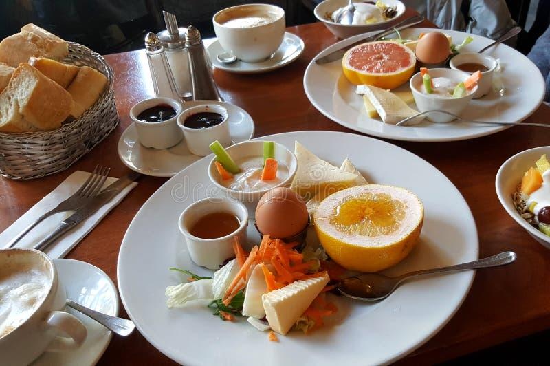 Sund frukost med frukt, ägg, ost, cappuccino, bröd, kaffe royaltyfri bild