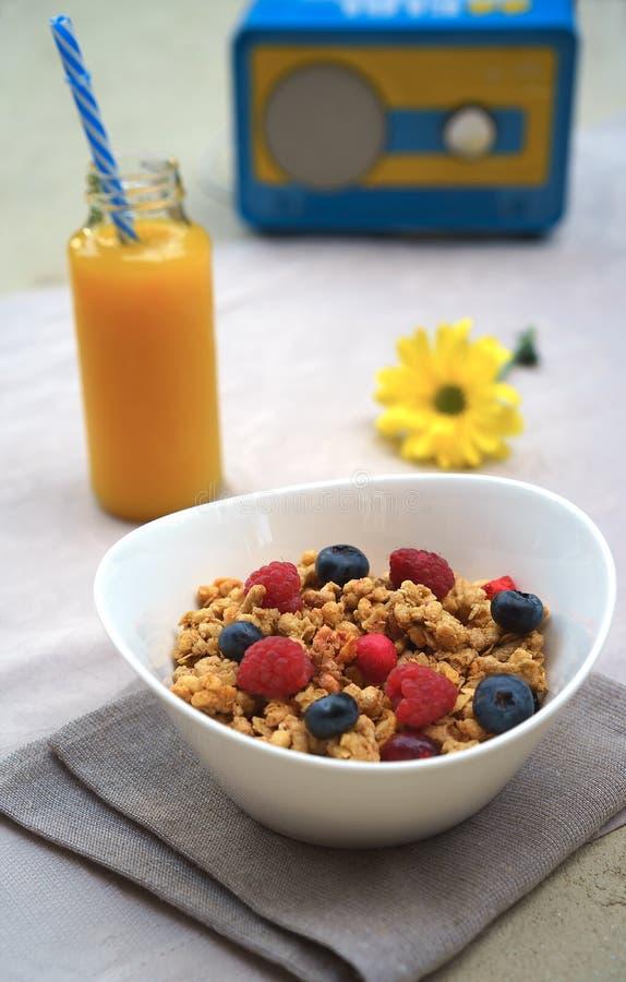 Sund frukost med granola, grekisk yoghurt, bär och ny orange fruktsaft på radiomottagaren i retro stilbakgrund royaltyfri foto