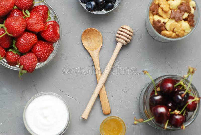 Sund frukost med havreflingor, naturlig yoghurt, nya blåbär, jordgubbar, mandlar och honung i Glass bunkar Lekmanna- lägenhet royaltyfri bild