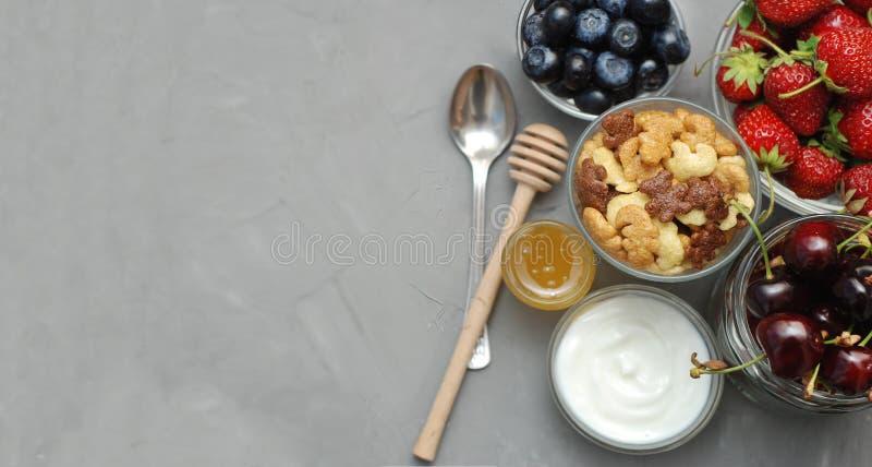 Sund frukost med havreflingor, naturlig yoghurt, nya blåbär, jordgubbar, mandlar och honung i Glass bunkar Lekmanna- lägenhet royaltyfri foto
