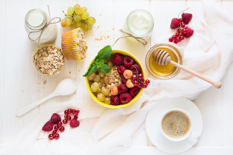 Sund frukost: mysli, honung, yoghurt, muffin, kaffe och nya bär arkivbild
