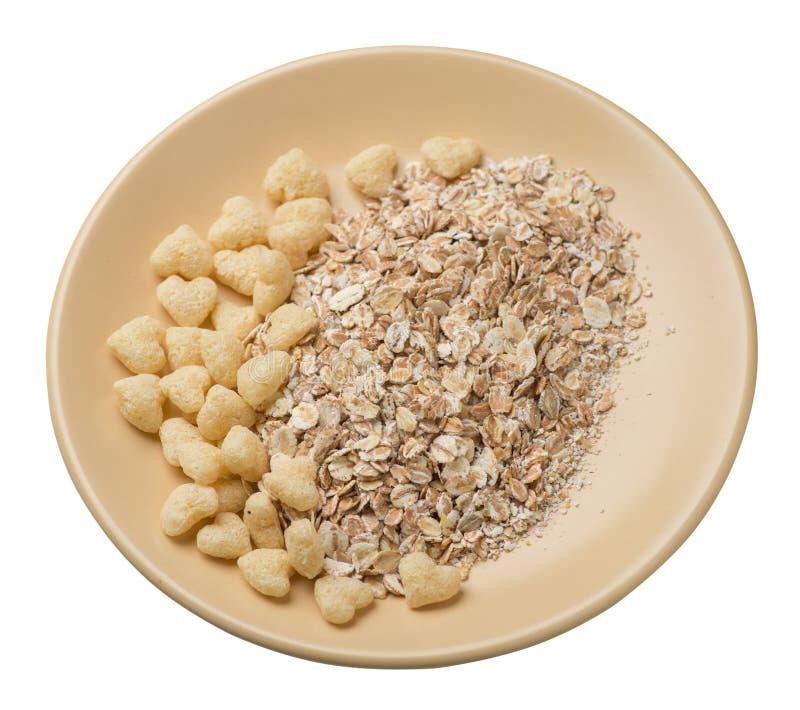 Sund frukost på en platta som isoleras på vit bakgrund myslit med cornflakes, russin, data, päron och ananas torkade arkivbilder