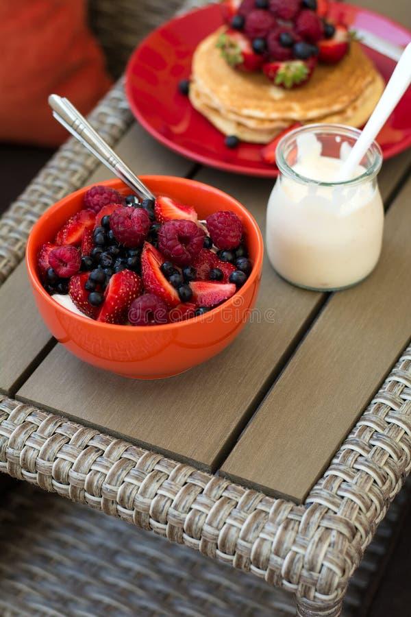 Sund frukost på trädgårds- möblemang: keso med gräddfil, jordgubben, hallonet och blåbäret, pannkakor, yoghurt royaltyfria bilder