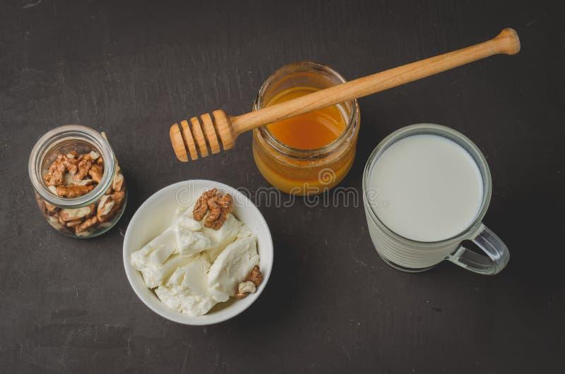 Sund frukostbakgrund Honung mjölkar, keso och valnöten på en stenbakgrund Top besk?dar arkivfoton