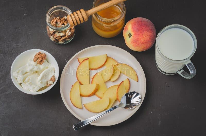 Sund frukostbakgrund Persikan honung, mjölkar, keso och valnöten på en stenbakgrund Top besk?dar arkivbilder
