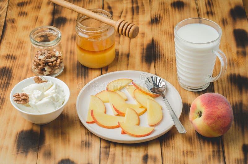 Sund frukostbakgrund Persikan honung, mjölkar, keso och valnöten på en trätabell royaltyfria bilder