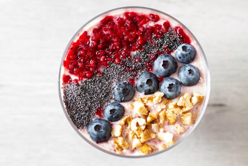 Sund frukostbunke: blåbärsmoothie med bananen, hallon, björnbär, muttrar på bästa sikt för tabell arkivfoton
