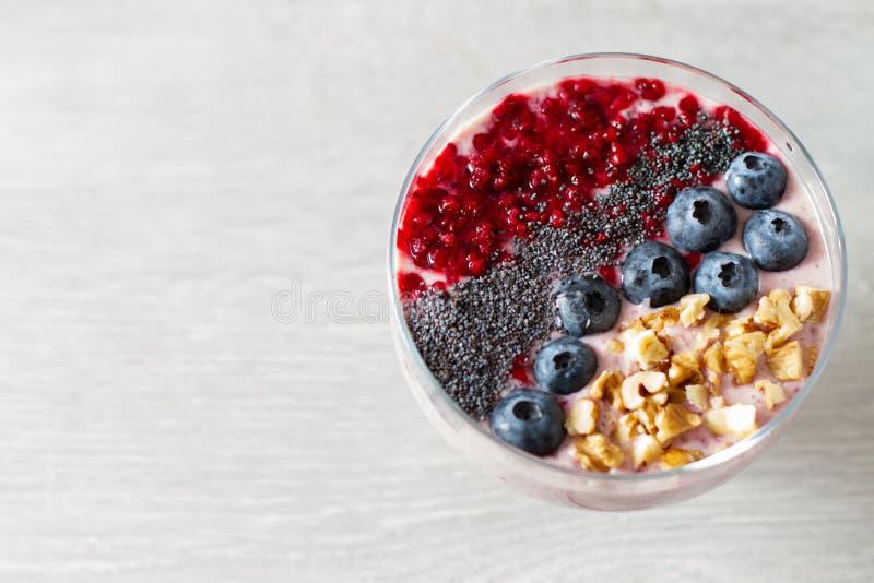 Sund frukostbunke: blåbärsmoothie med bananen, hallon, björnbär, muttrar på den vita tabellen arkivbild