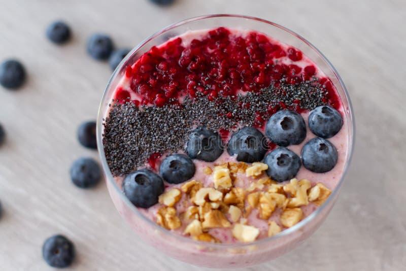 Sund frukostbunke: blåbärsmoothie med bananen, hallon, björnbär, muttrar på tabellen arkivbilder