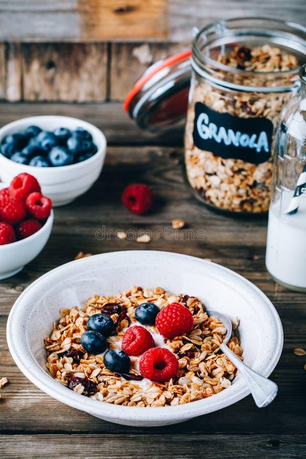 Sund frukostbunke Hemlagad granola med naturliga yoghurt, blåbär och hallon arkivbilder