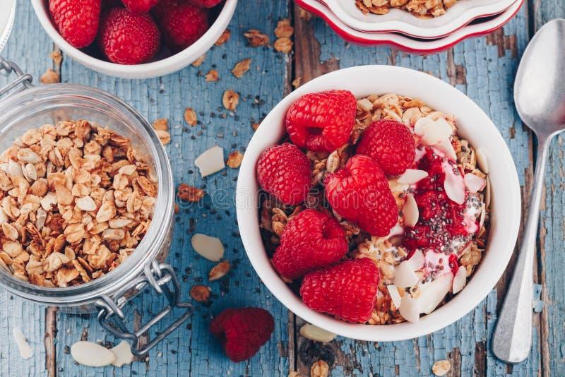 Sund frukostbunkegranola med grekisk yoghurt, nya hallon och chiafrö arkivfoton