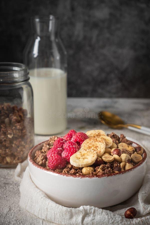 Sund frukostgranola i en platta med muttrar, banan och hallon, mjölkar hälls från en flaska royaltyfri fotografi
