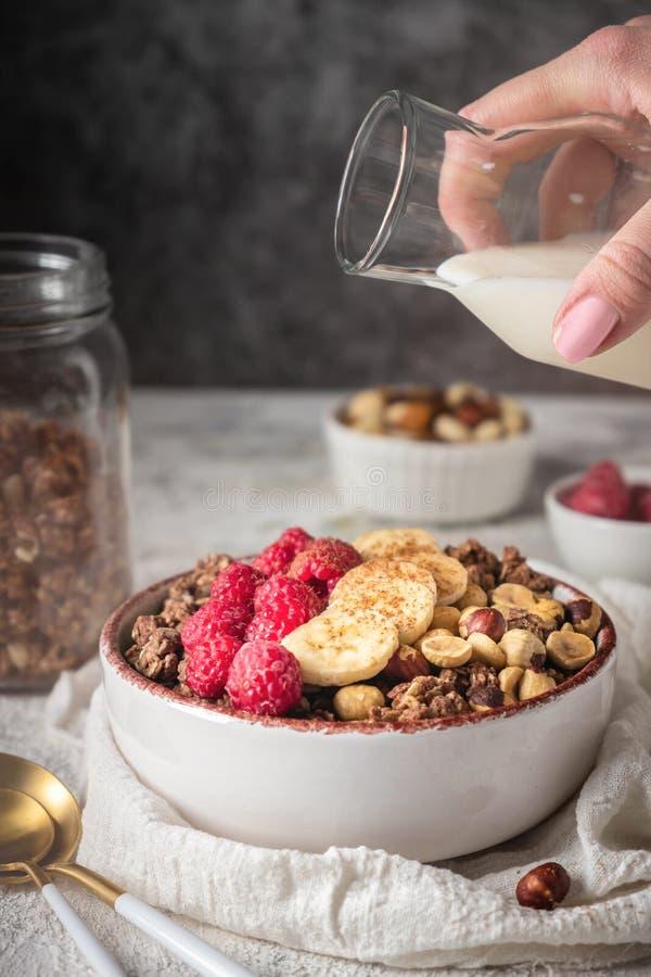 Sund frukostgranola i en platta med muttrar, banan och hallon, mjölkar hälls från en flaska royaltyfria foton