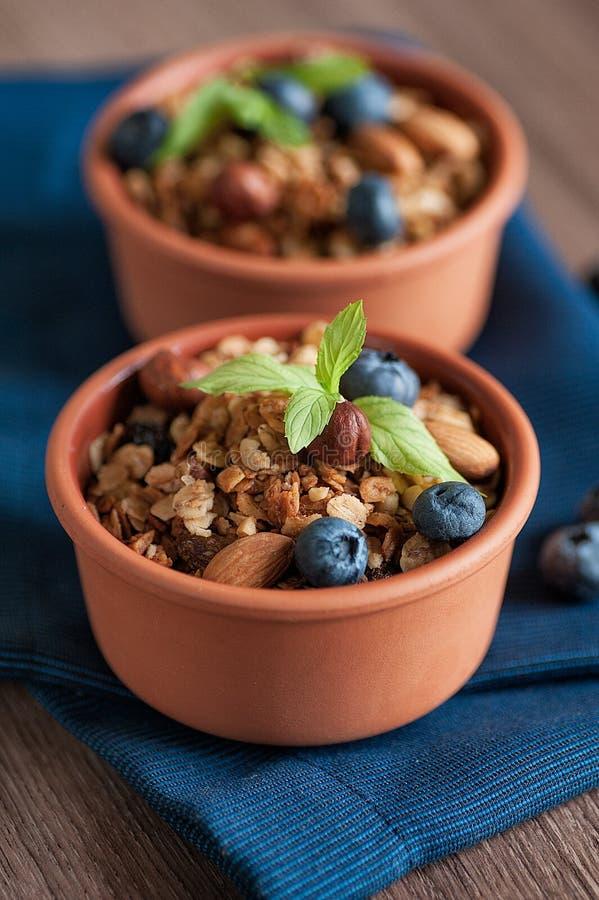 Sund frukostGranola med keramiska plattor för ny blueberriein över träyttersida royaltyfria foton