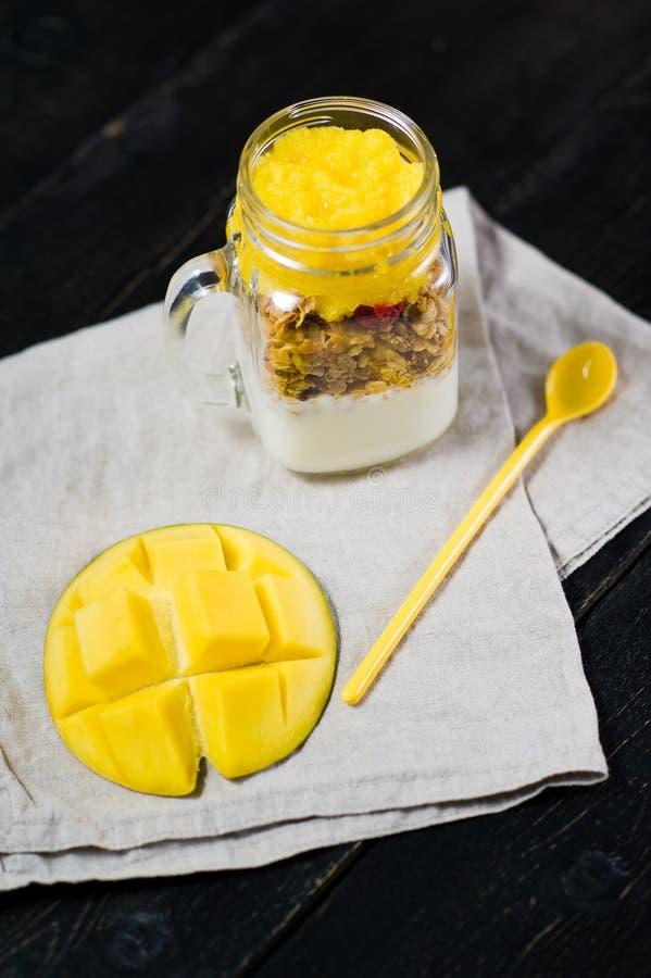 Sund frukostmysli och yoghurt med mangosmoothien i exponeringsglasmurarekrus fotografering för bildbyråer
