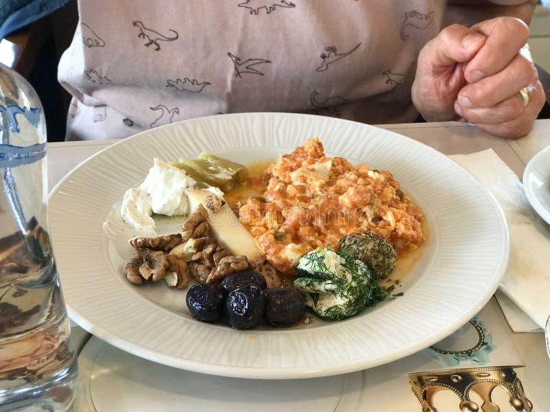 Sund frukostplatta med förvanskade ägg, oliv, valnöten, yoghurt och kryddig ost fotografering för bildbyråer